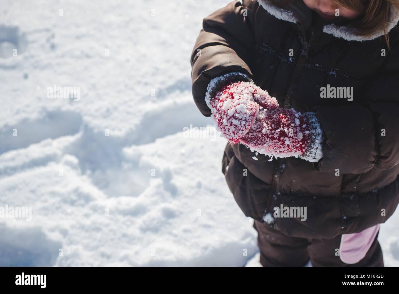 Un niño de 3 años vistiendo la ropa de invierno, guantes de invierno, juega en la nieve en un soleado Imagen De Stock