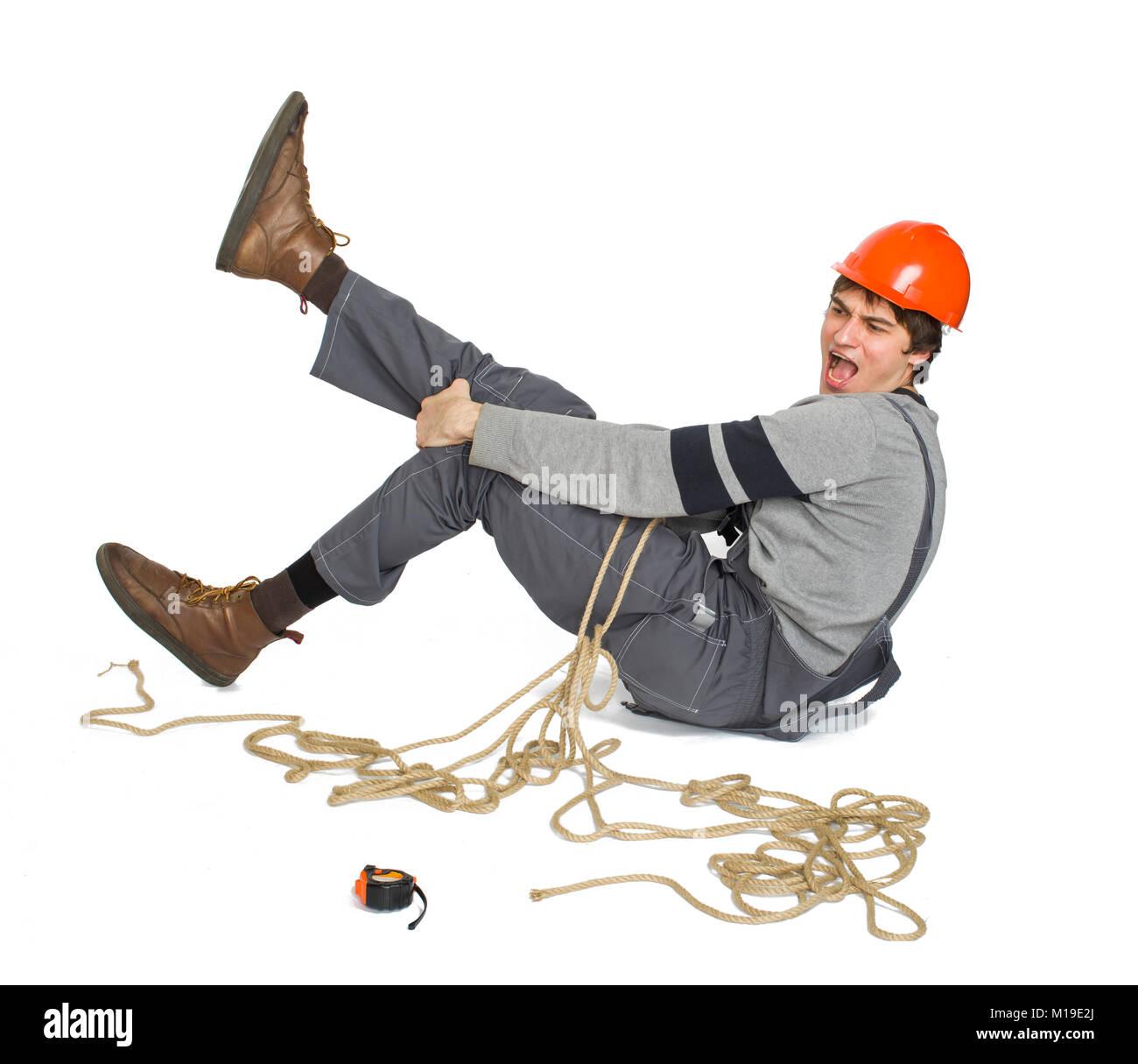 Un joven trabajador en uniforme gris atada con cuerdas sobre fondo blanco aisladas. Foto de stock