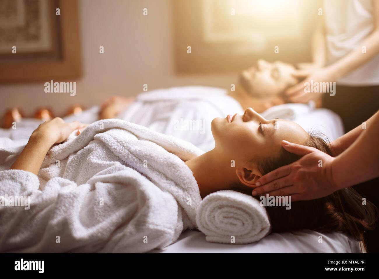 Hermosa joven feliz pareja disfrutando de un masaje en el spa de cabeza Imagen De Stock