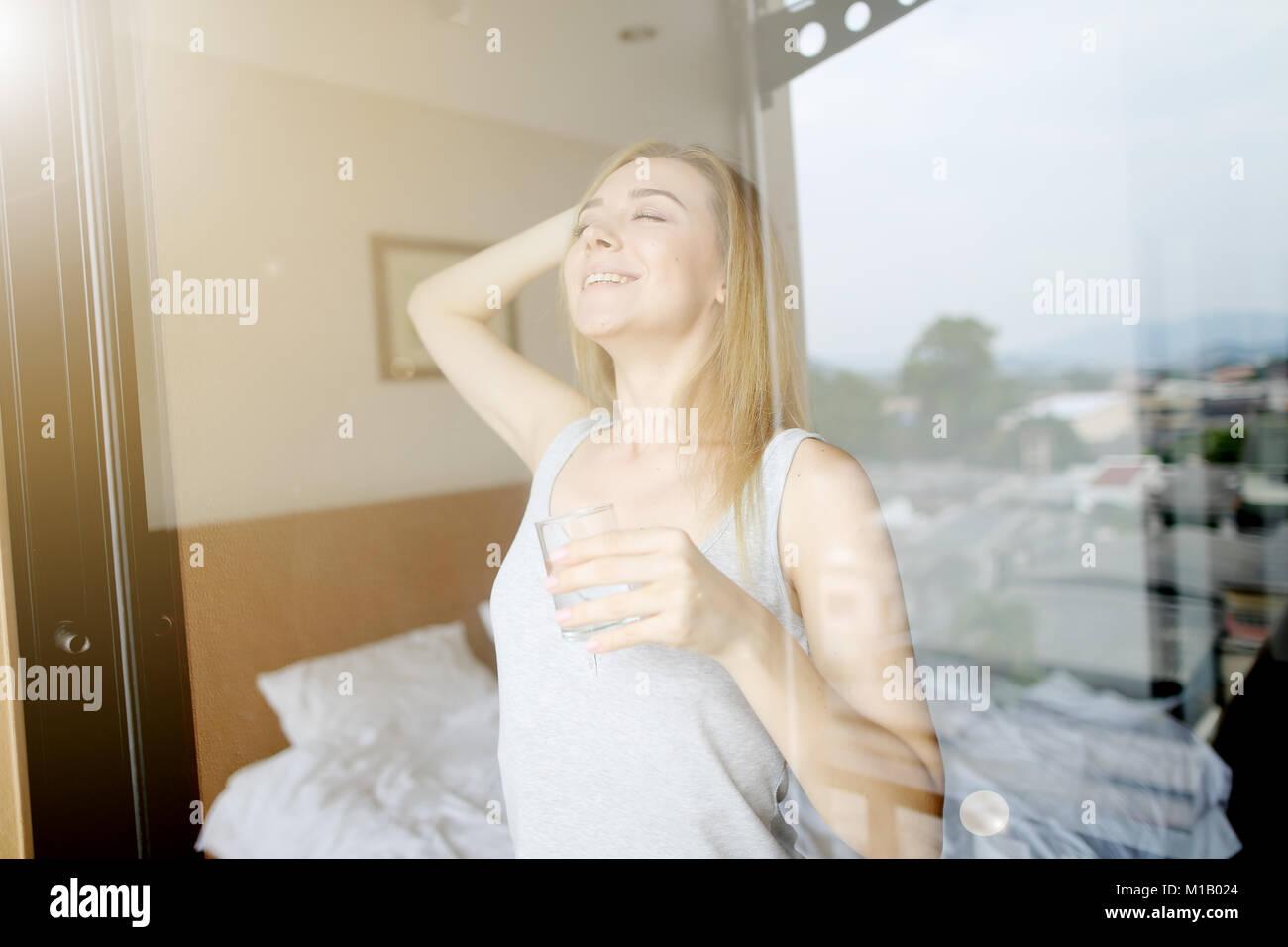 La mujer es el estiramiento después de dormir con un vaso de agua Imagen De Stock