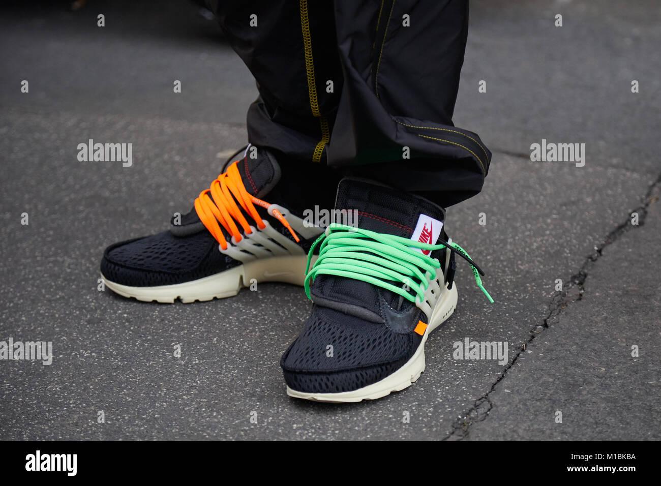 b03594716 Milán - 15 de enero  el hombre con zapatillas Nike negras con naranja y  verde los cordones antes de representar el Fashion Show