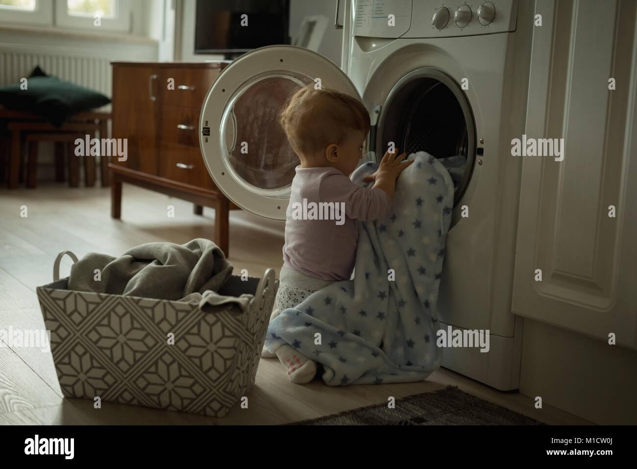 Bebé poniendo la ropa dentro de la lavadora Imagen De Stock