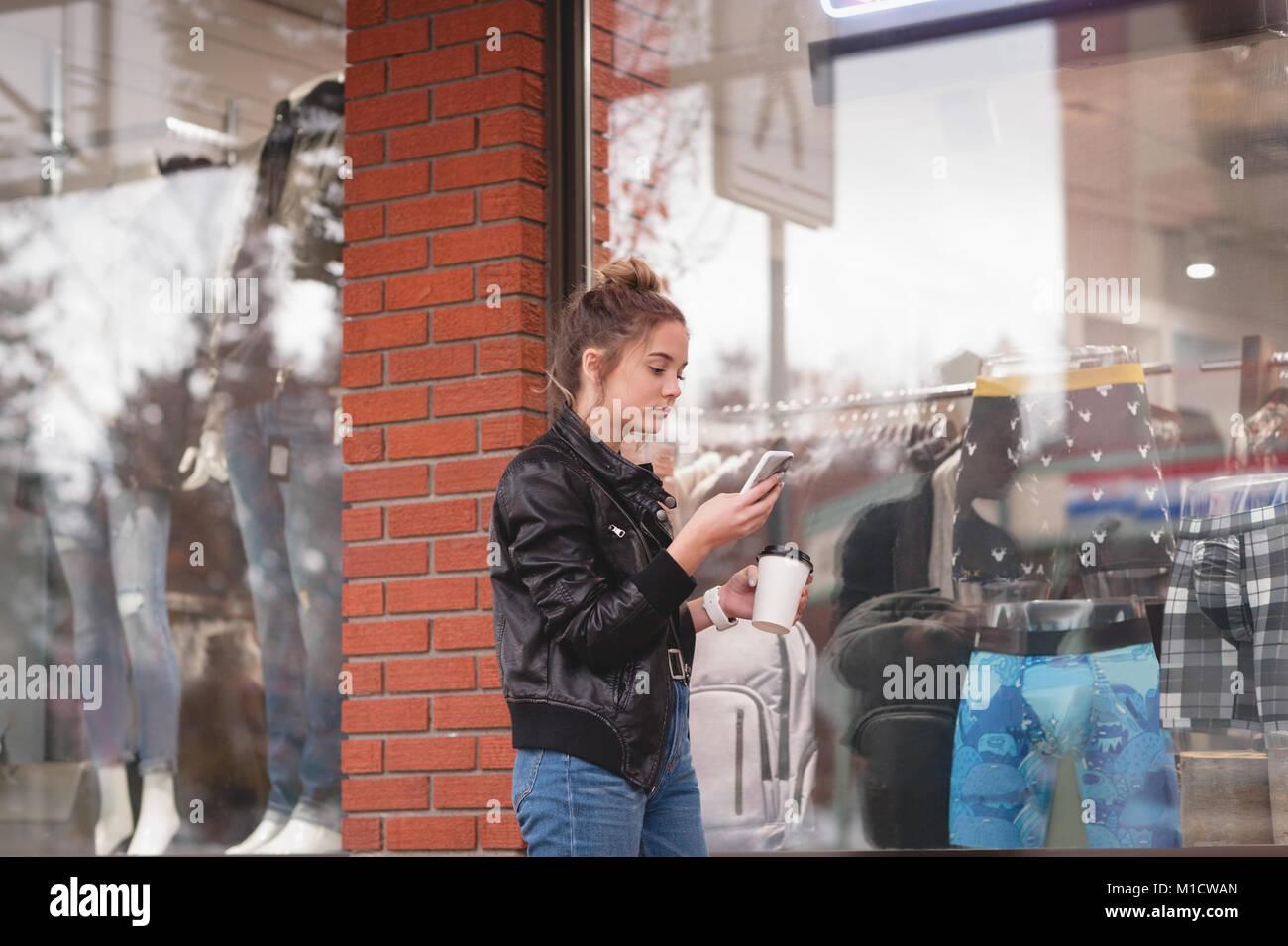 Mujer hermosa a través de teléfono móvil mientras tomábamos café Foto de stock