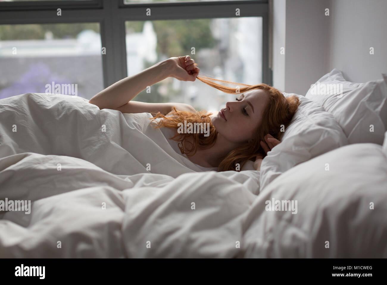 Mujer relajante en la cama en el dormitorio en el hogar Imagen De Stock