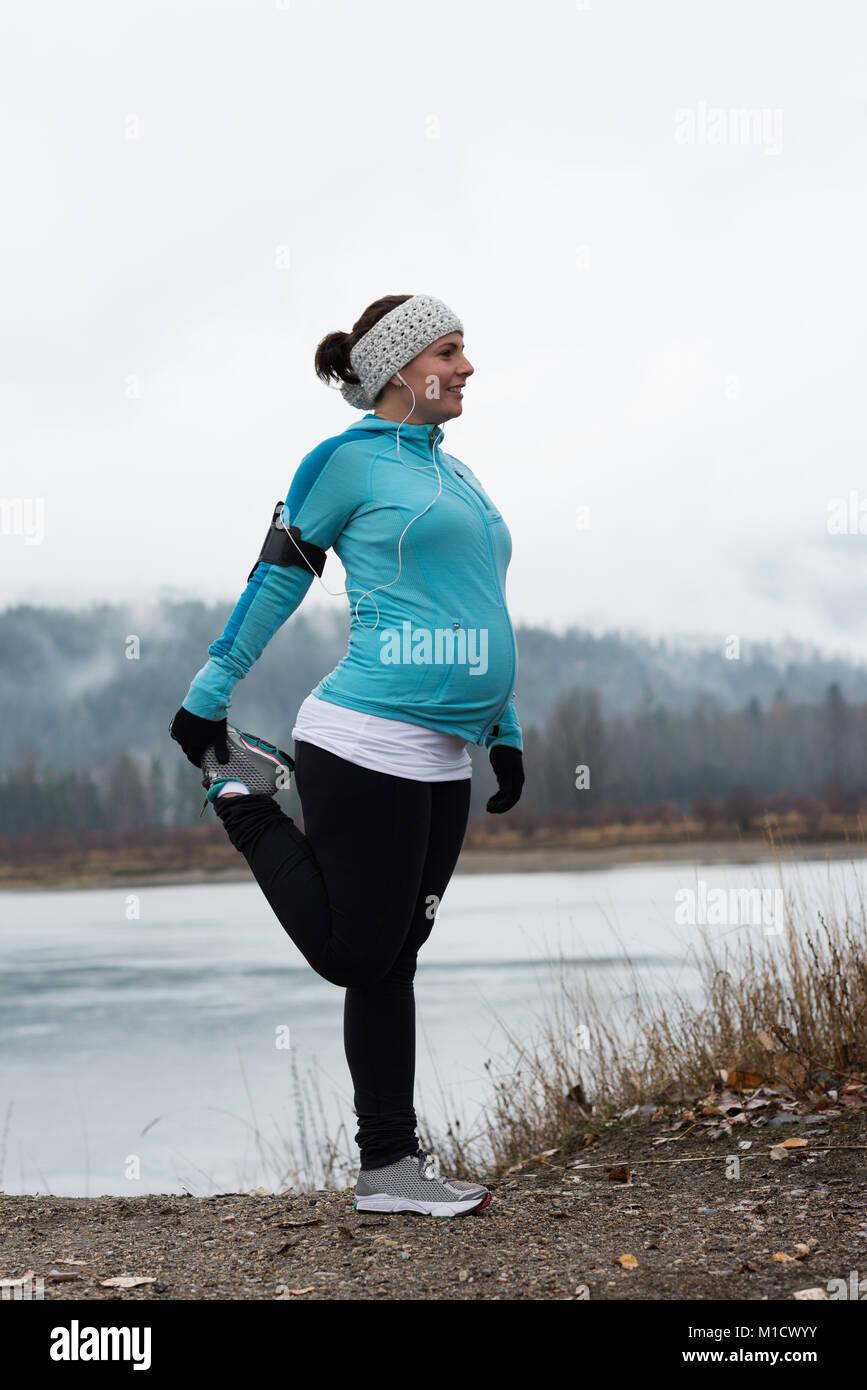 Mujer embarazada realizar ejercicio de estiramiento Imagen De Stock