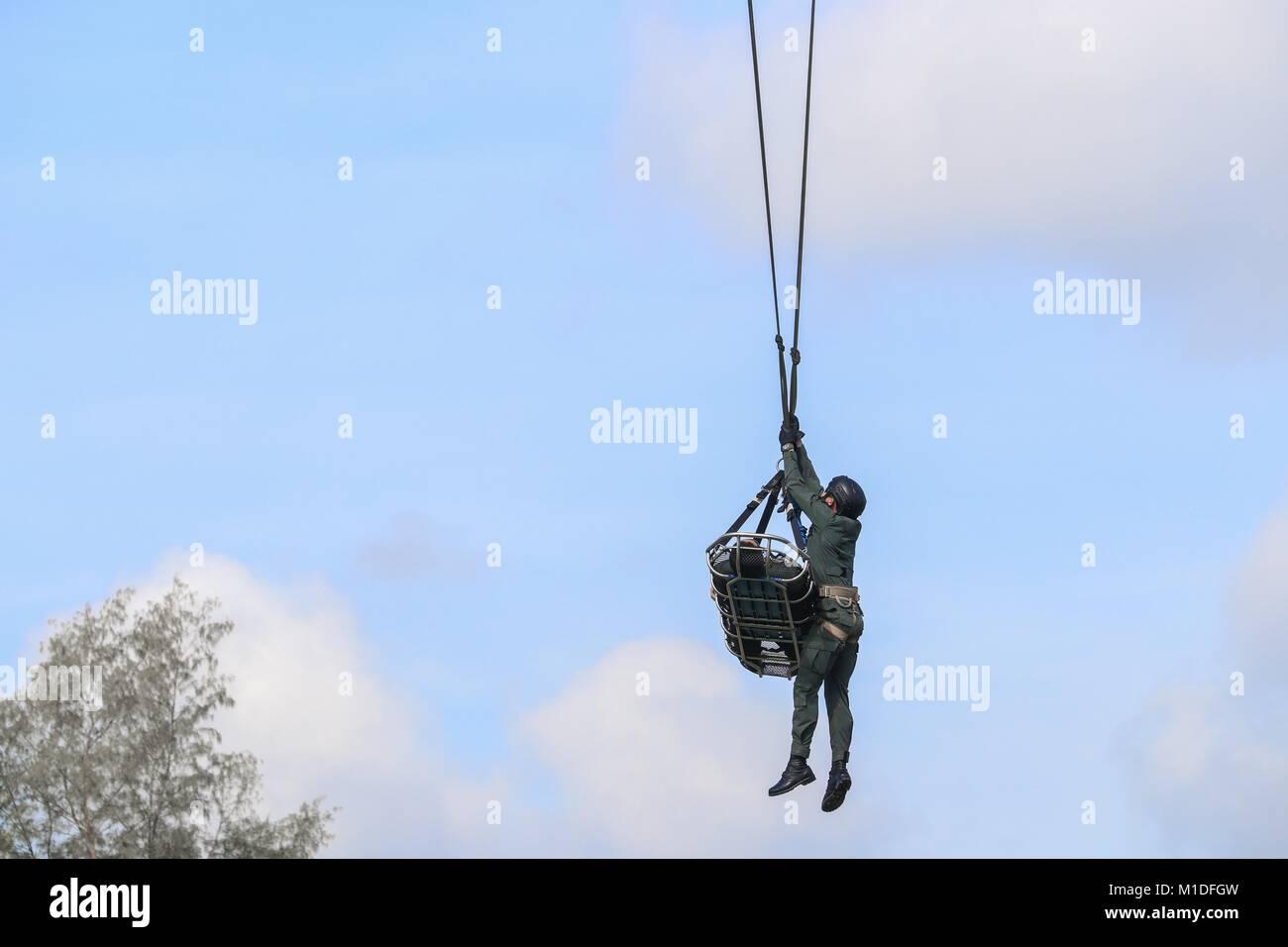Soldado de emergencia de rescate por helicóptero del ejército con cuerda en blue sky Imagen De Stock