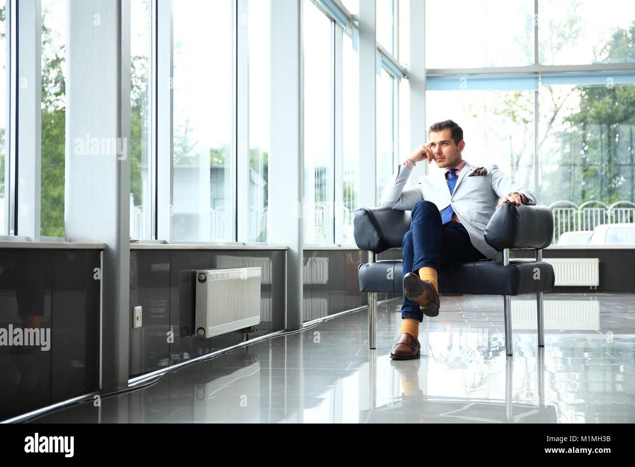 Un ángulo bajo la foto de un apuesto joven empresario en un moderno espacio de oficina con grandes ventanales. Foto de stock