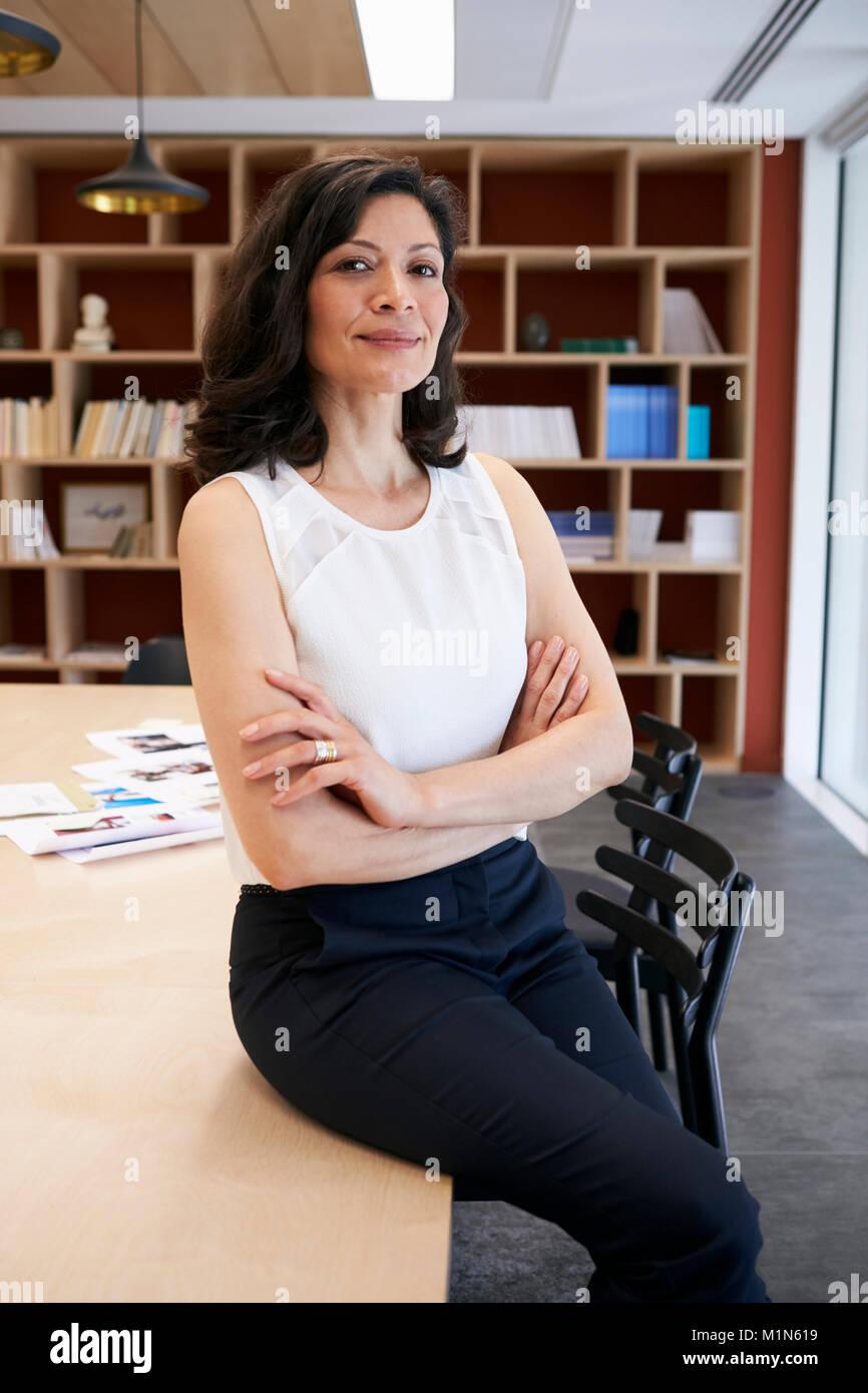 Creative hembra de mediana edad sentado en el escritorio en una oficina. Imagen De Stock
