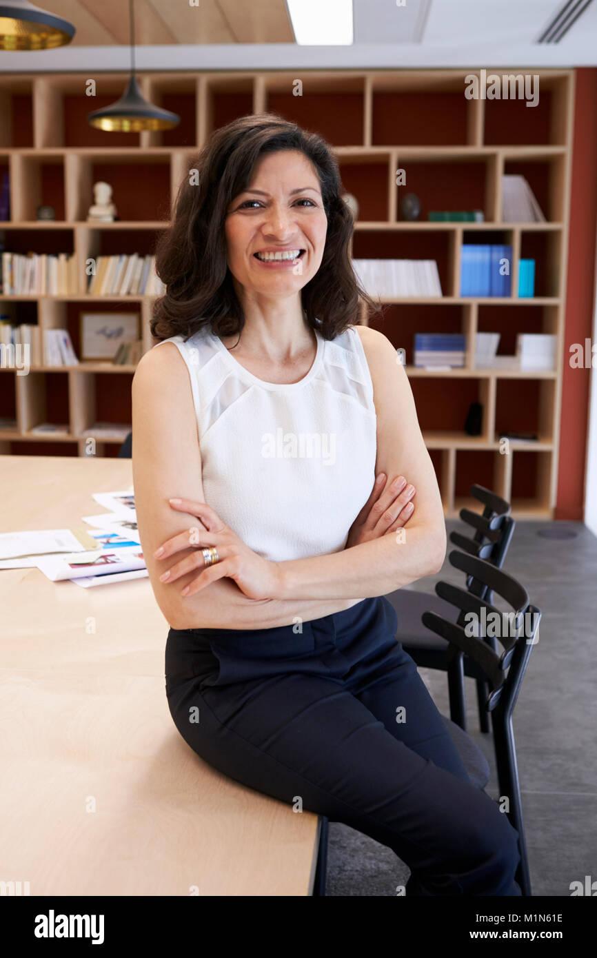 Mujer de mediana edad sentada en su escritorio creativo sonríe a cámara Imagen De Stock