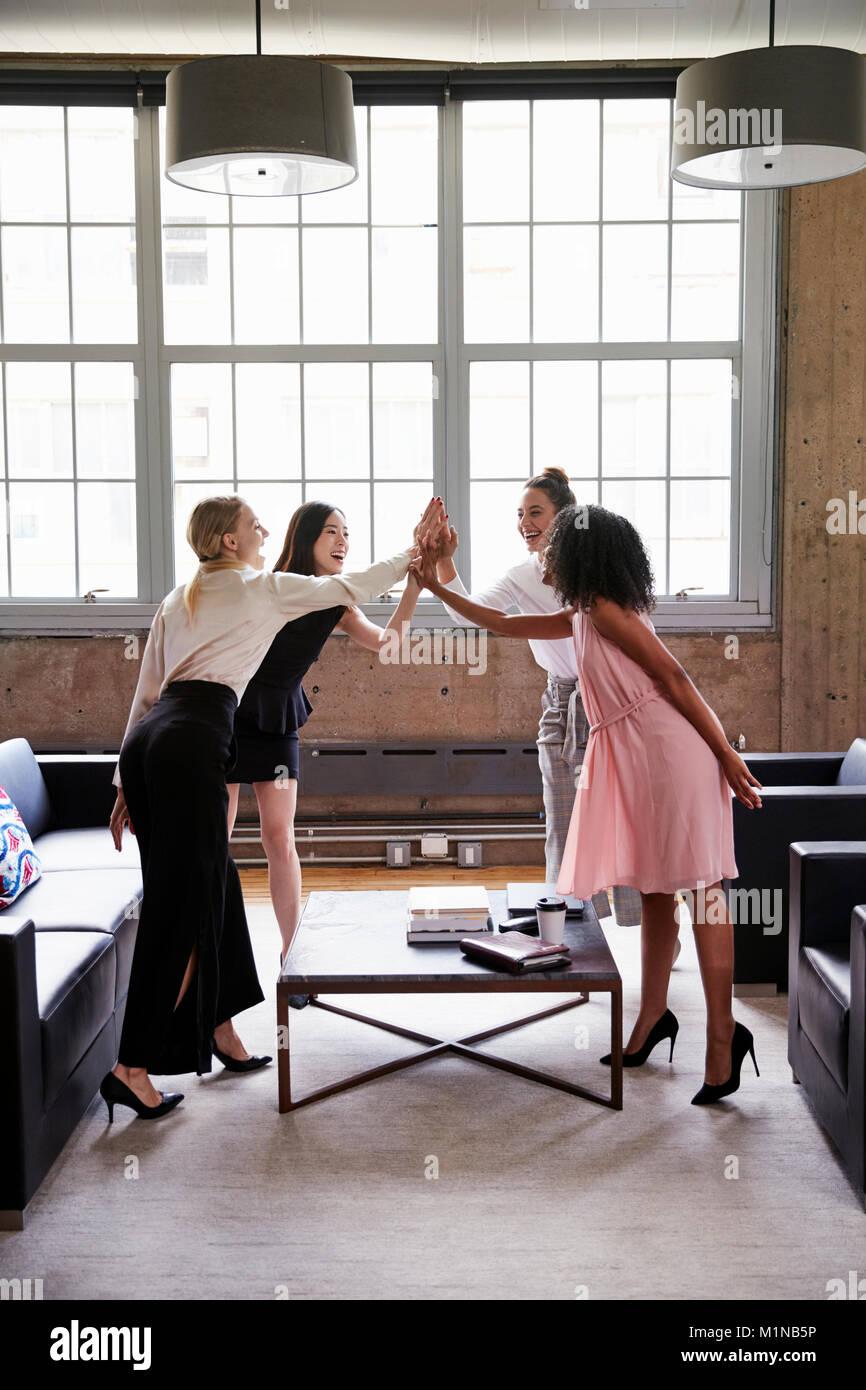 Alta cinco compañeras en una reunión casual, vertical Imagen De Stock