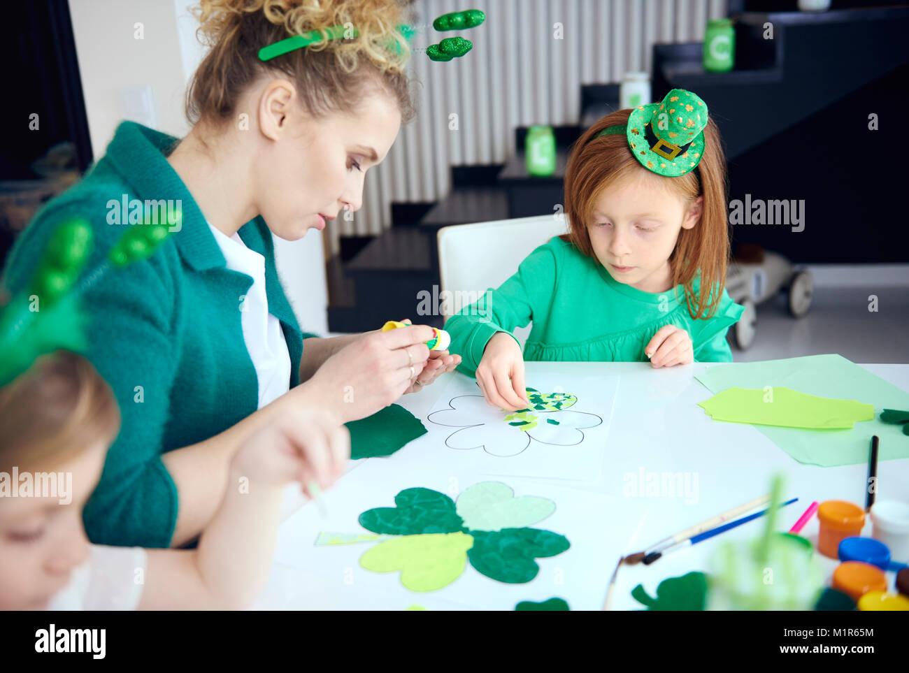 Mujer con chicas haciendo ornamento en Saint Patrick's day Imagen De Stock