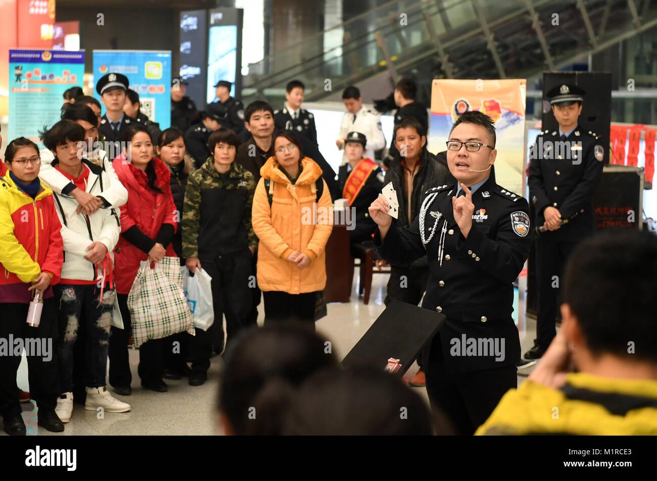 Nanning, China la provincia de Guangxi. 1 Feb, 2018. Un oficial de policía advierte a los pasajeros de engañoso Imagen De Stock