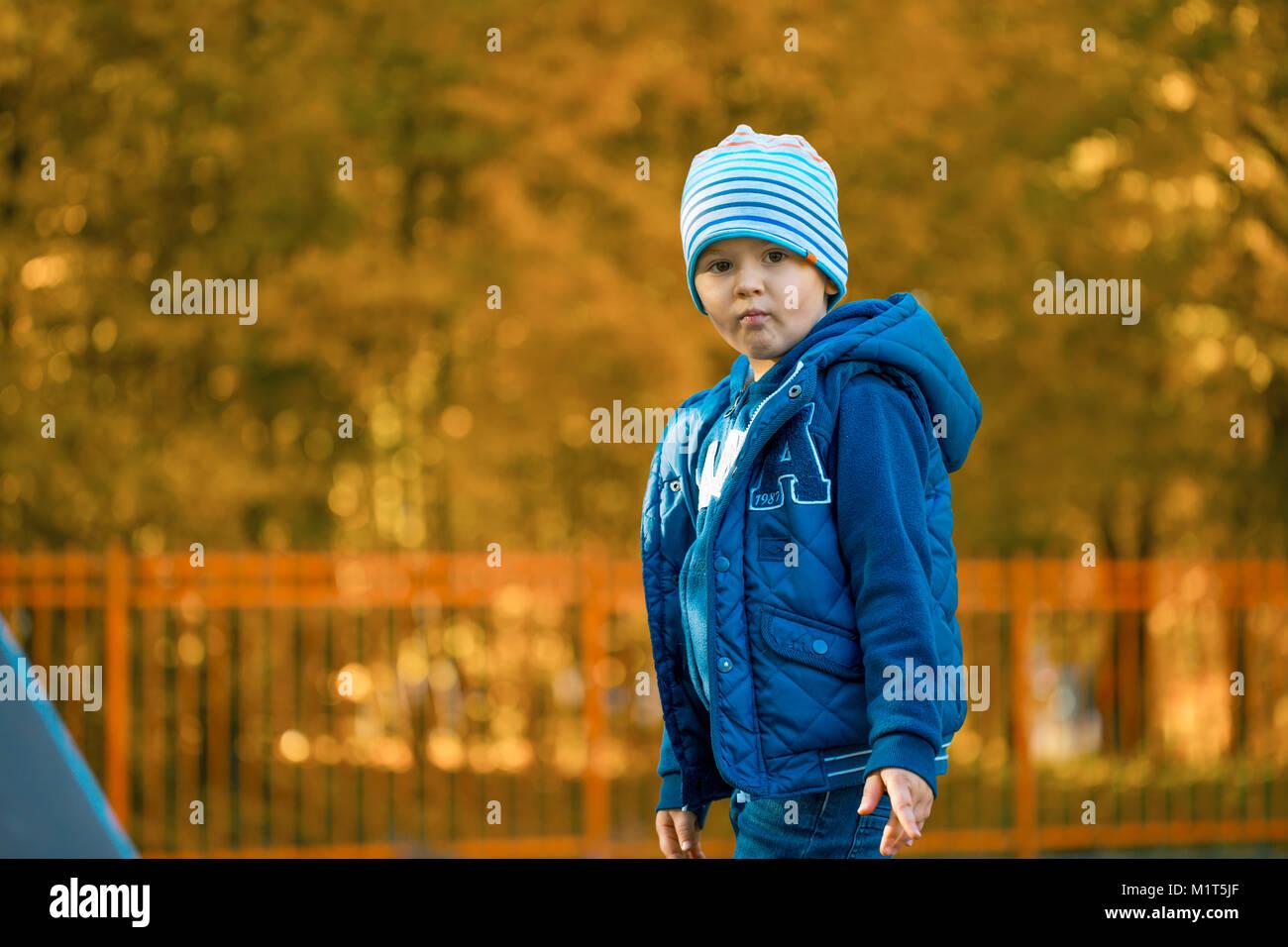 Cute Baby Boy de pie en el parque de otoño Imagen De Stock