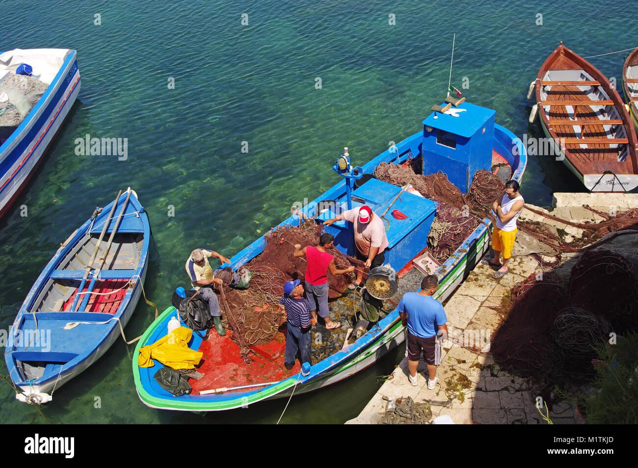 Los hombres de pesca ordenar las redes de pesca, Seno Della Purita Harbor, Gallipoli, Apulia, en el sur de Italia Imagen De Stock