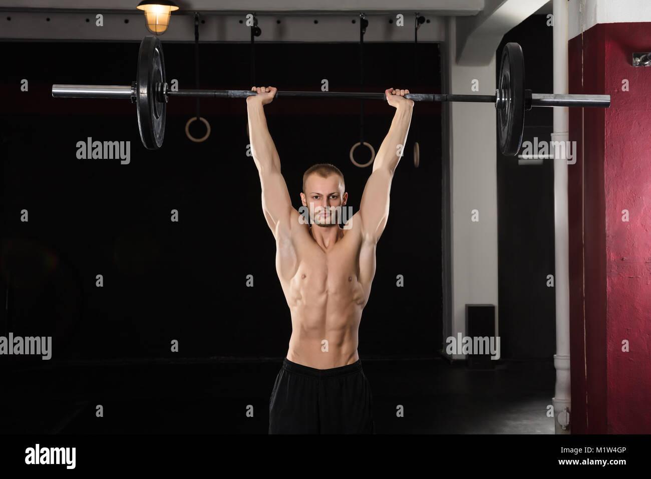 Retrato de un joven atleta hombre levantando Barbell En el gimnasio. Foto de stock