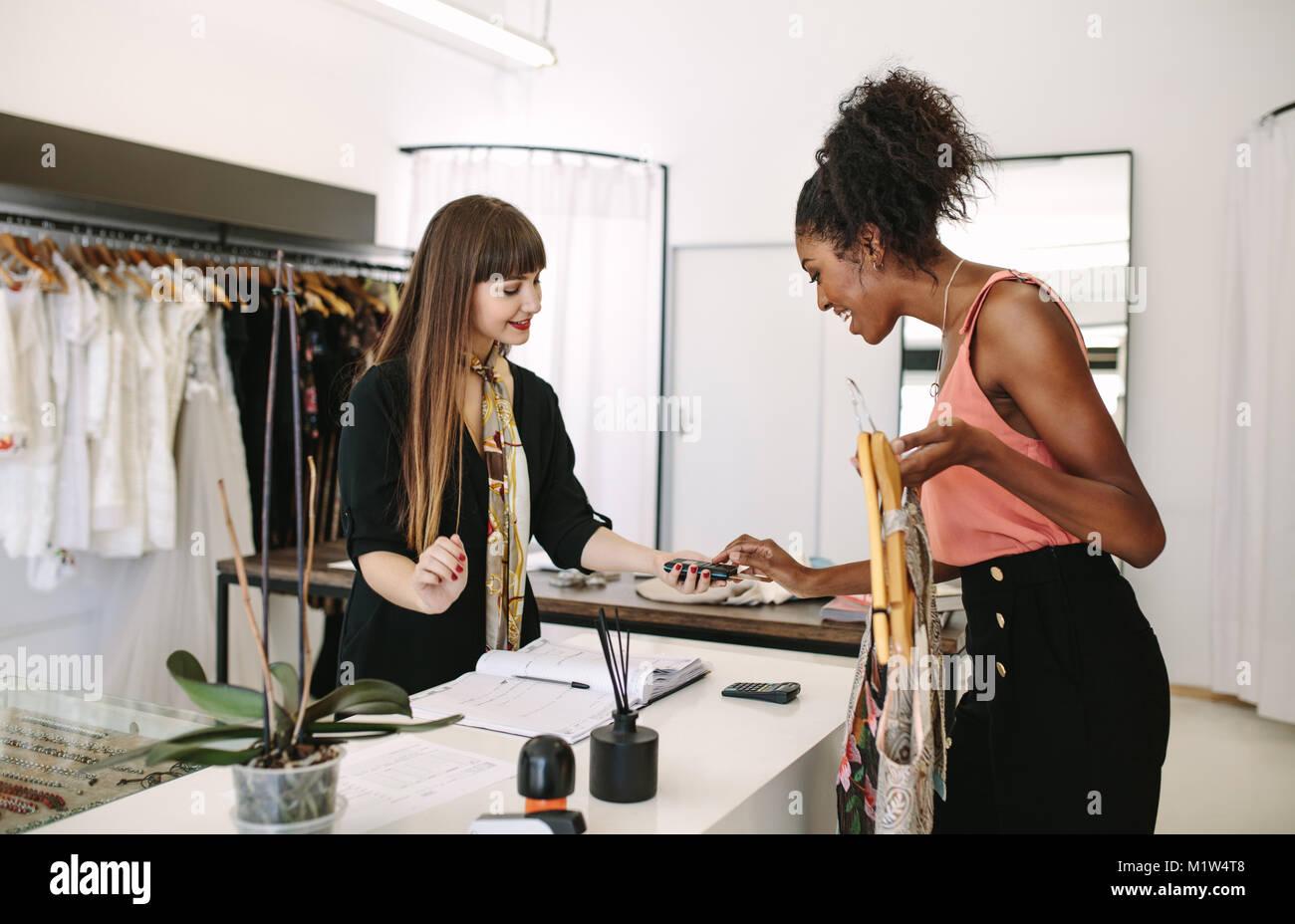 Diseñador de compras del cliente desgaste en una boutique de moda. El cliente, haciendo el pago introduciendo Imagen De Stock