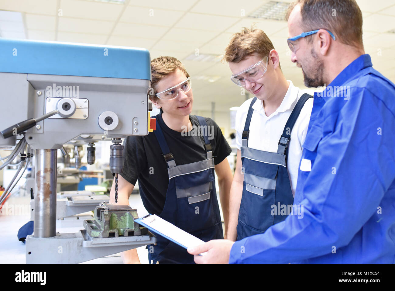 Formador y aprendiz en la formación técnica en máquina de perforación Imagen De Stock