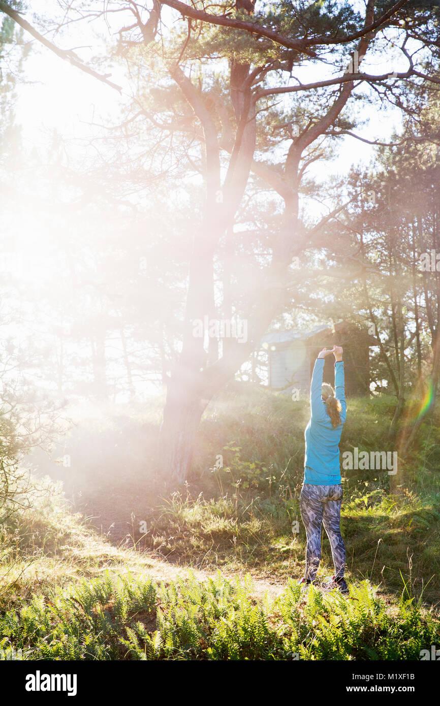 Mujer estirando el sendero del bosque en Sandhammeren, Suecia Imagen De Stock