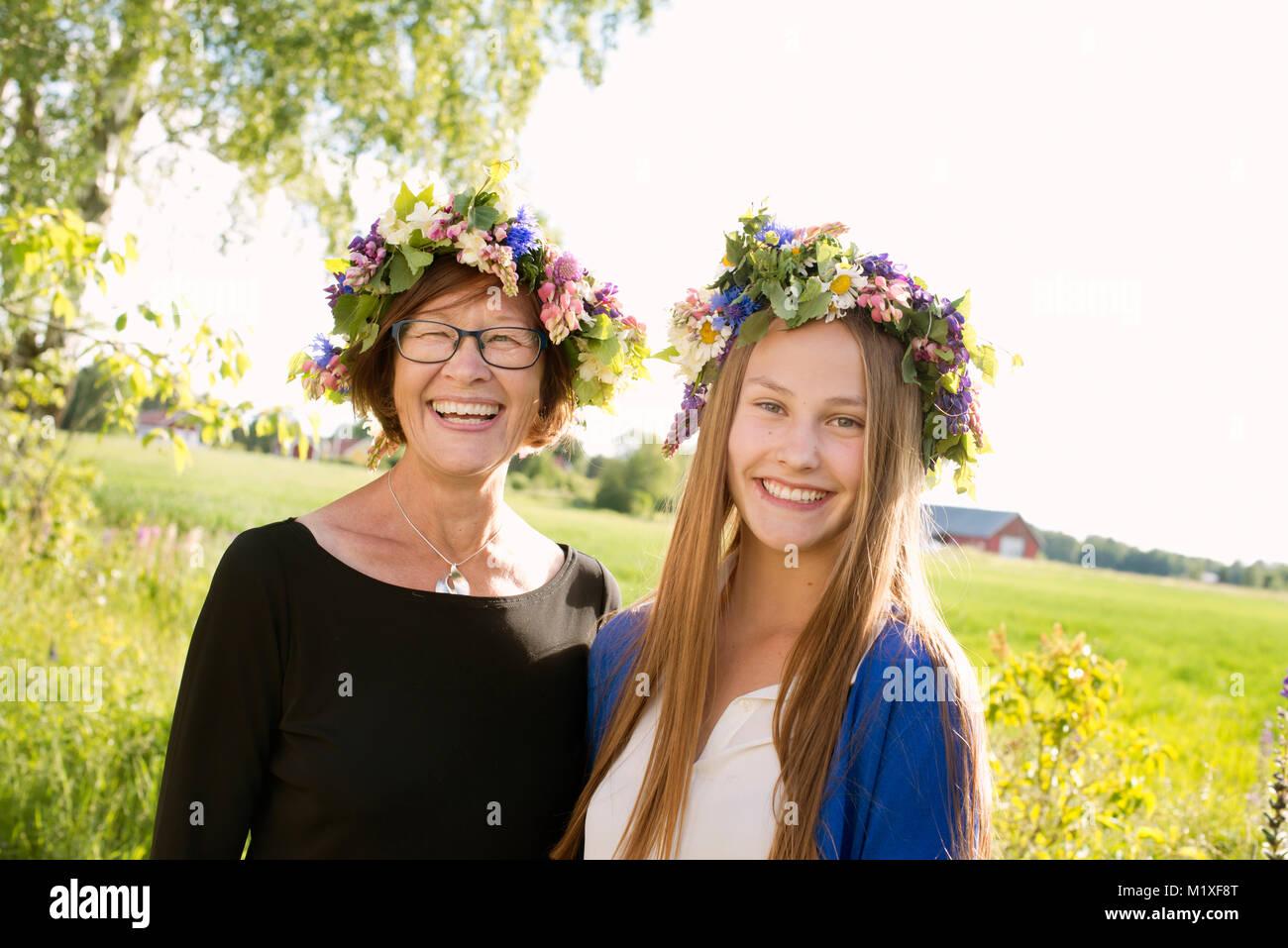 Chica y su abuela vistiendo midsummer coronas en Kallandso, Suecia Foto de stock