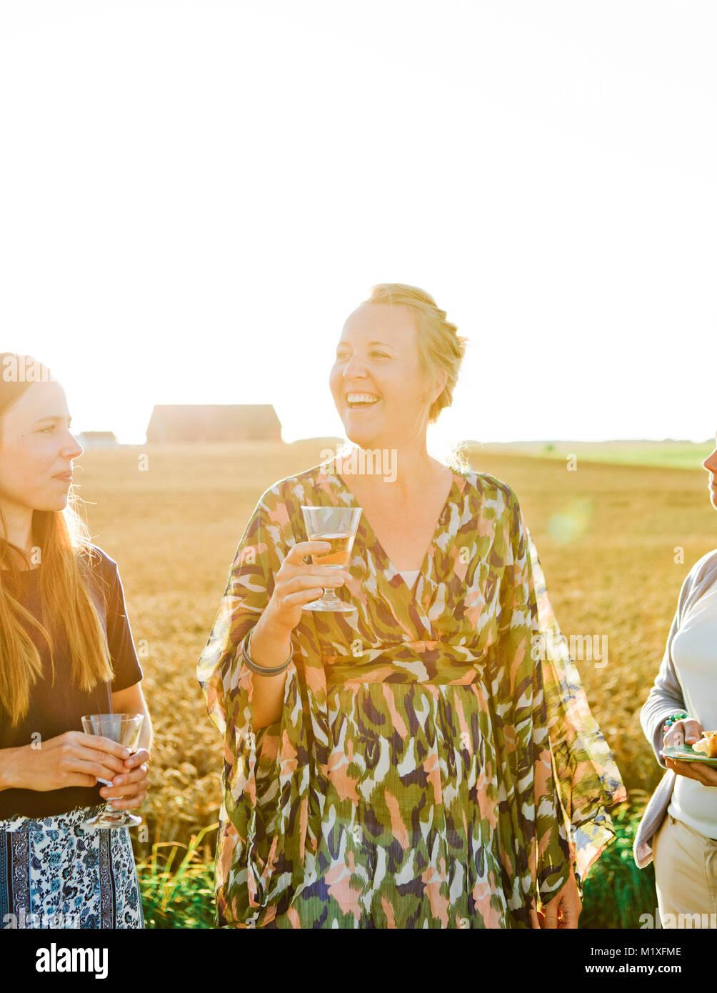 Amigos bebiendo vino al atardecer en Friseboda, Suecia Imagen De Stock