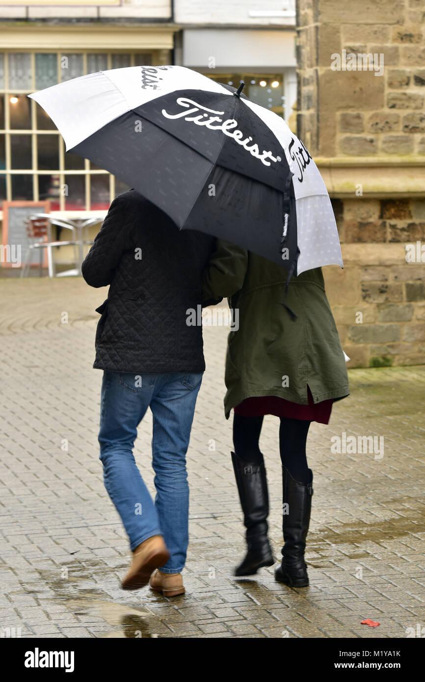 Una pareja caminando en la torrencial lluvia torrencial compartiendo una gran sombrilla de golf en blanco y negro. Imagen De Stock