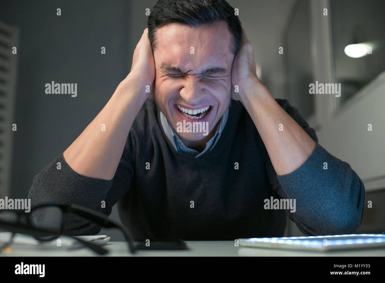 Estresante guapo cerrando los oídos Imagen De Stock