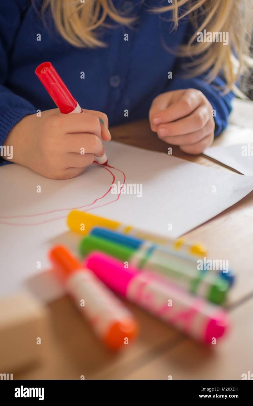 Niña de dibujo con lápices de colores brillantes Foto de stock