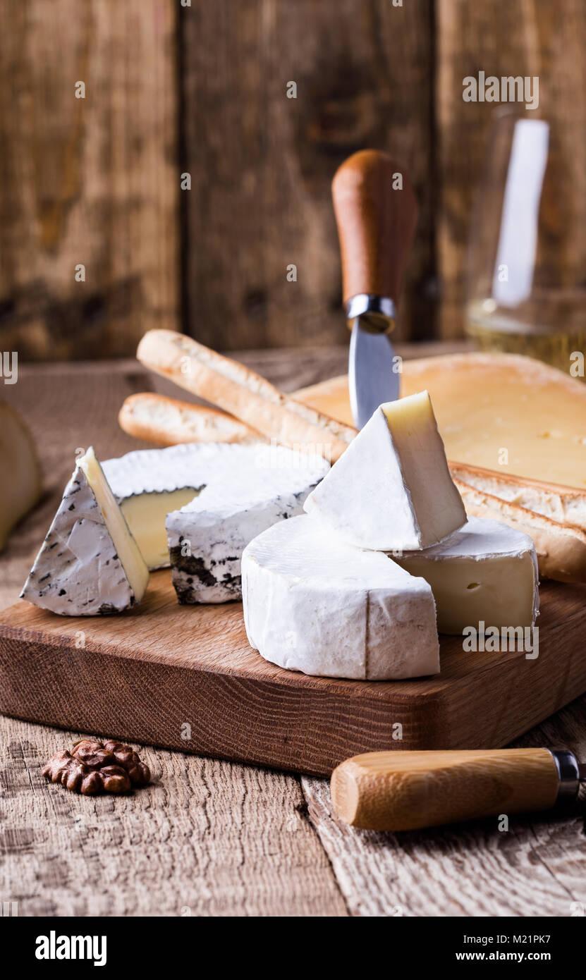 Junta con distintos tipos de queso en la mesa de madera rústica Imagen De Stock