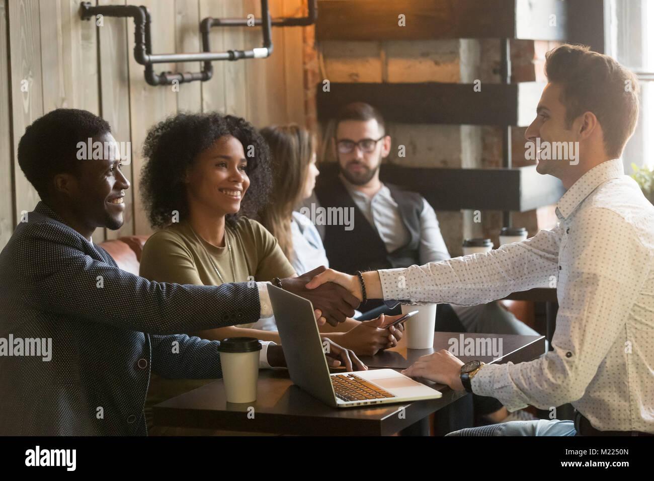 Los hombres caucásicos y africanos multirracial handshaking en una reunión celebrada en Imagen De Stock