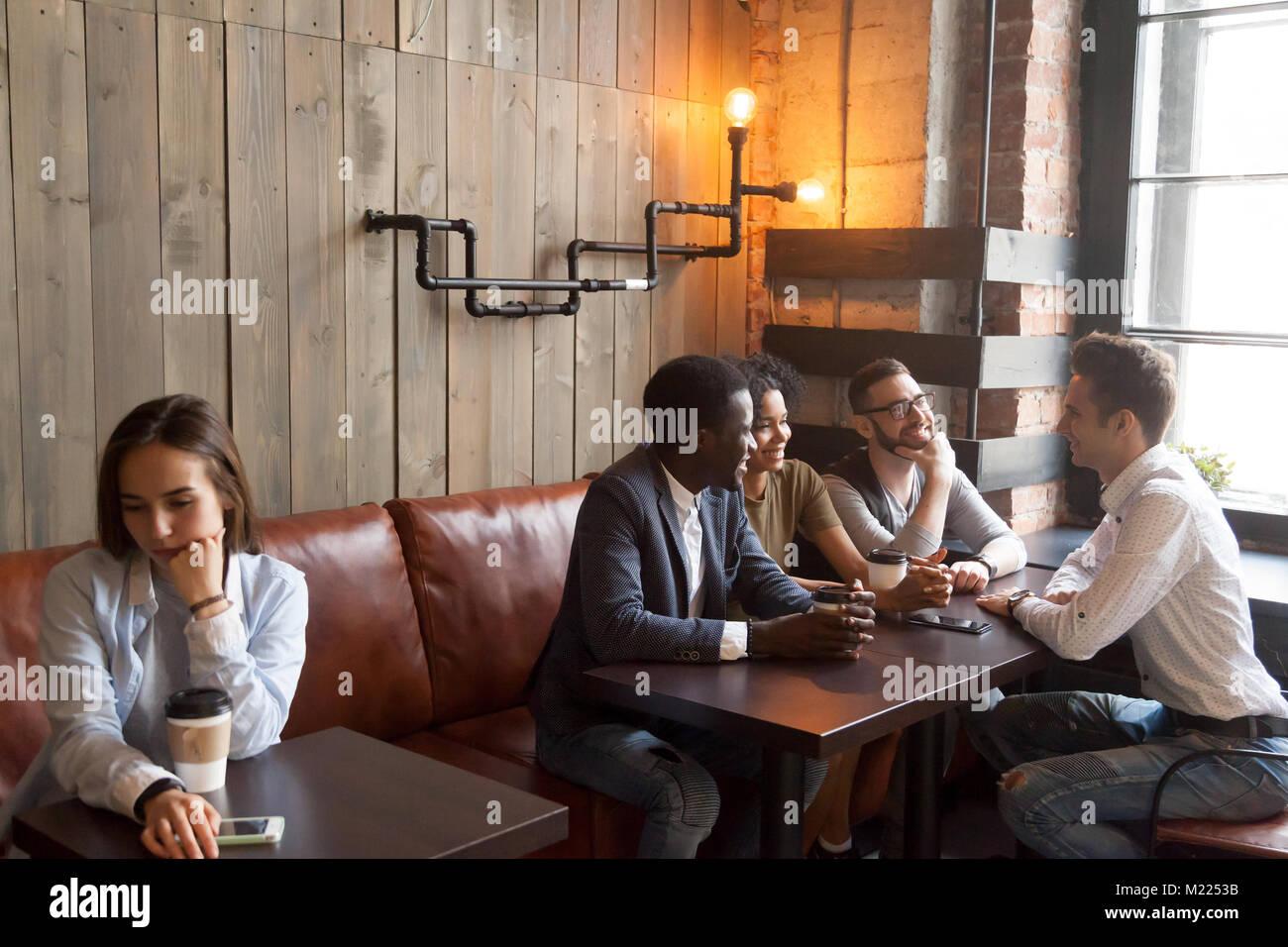 Diversos jóvenes amigos ignorando triste chica sentada sola en el cafe Imagen De Stock