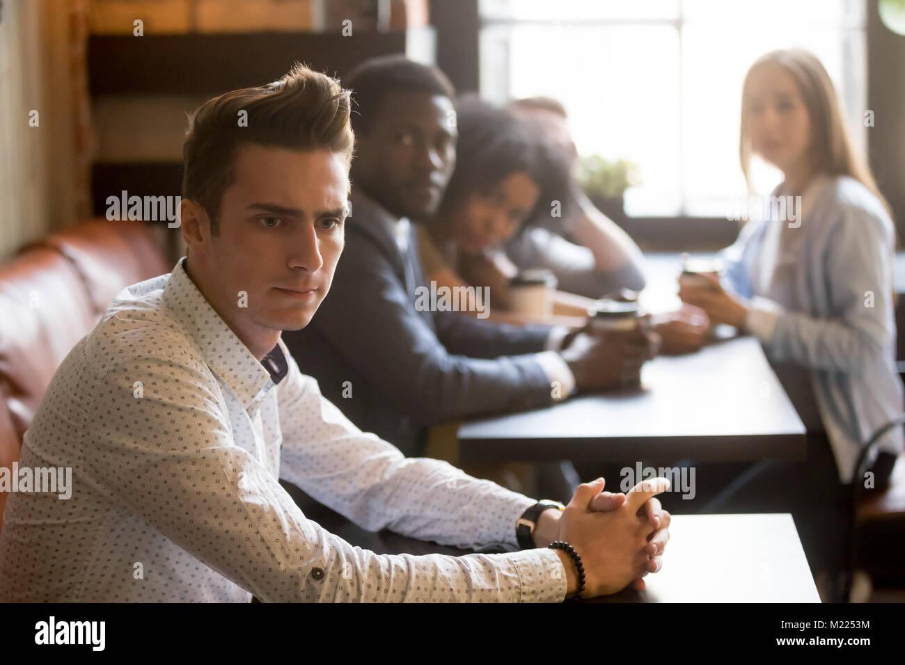 Diversos amigos viendo frustrado el hombre sentado solo en cafe Imagen De Stock