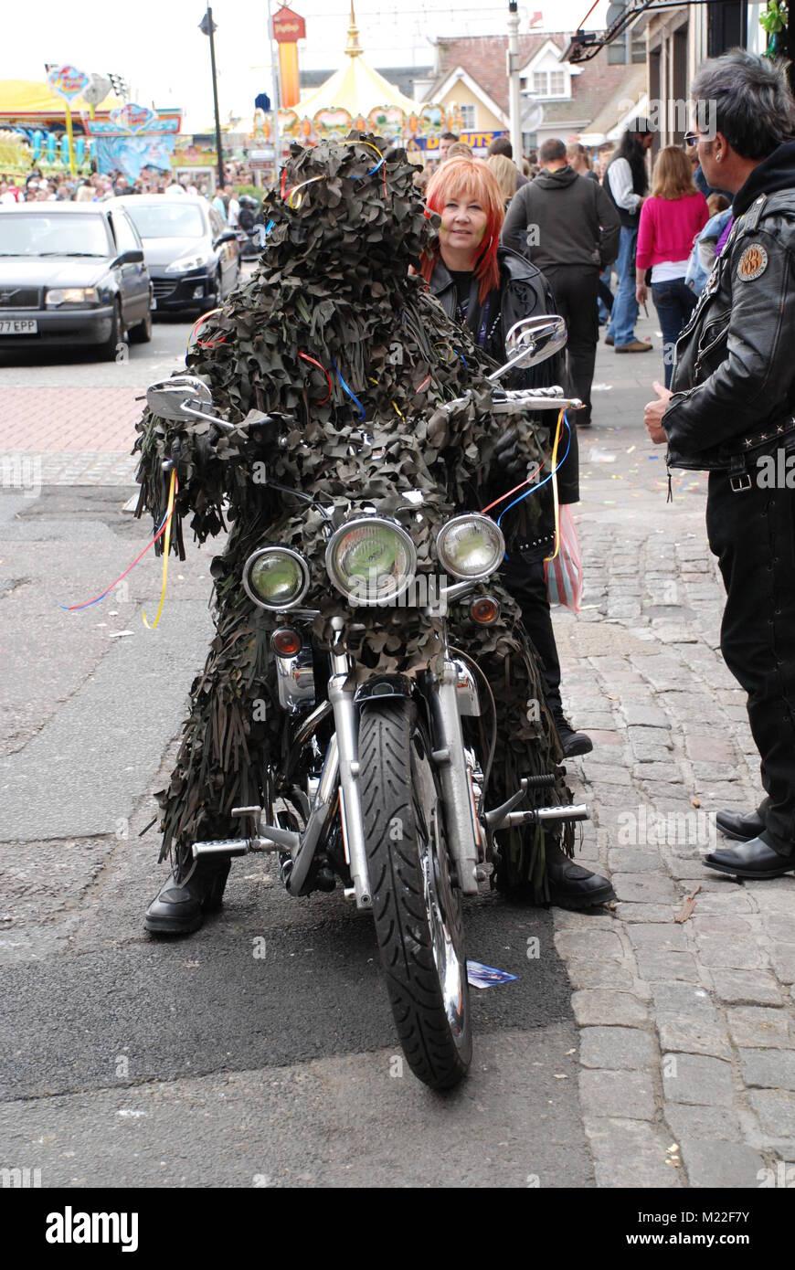 Un hombre en un traje de hojas se asienta en una motocicleta durante el día del gato en el Green Festival y Imagen De Stock