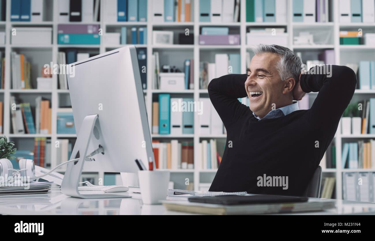 Seguro empresario sonriente relajado en su oficina con las manos detrás de la cabeza: negocio exitoso y logro Imagen De Stock