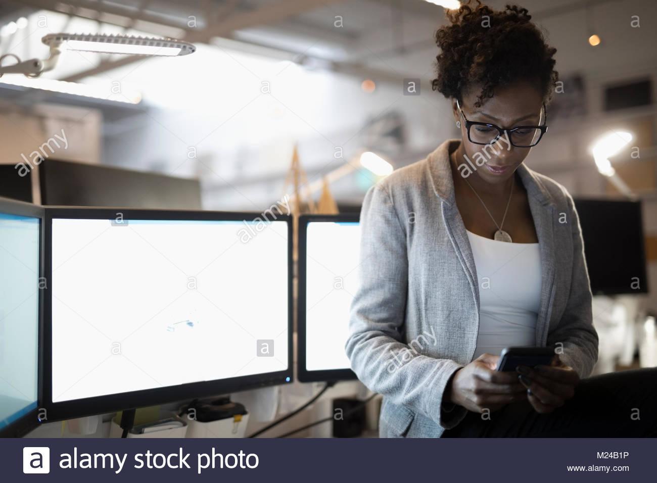 Empresaria dedicada al teléfono inteligente utilizando equipos de oficina Imagen De Stock