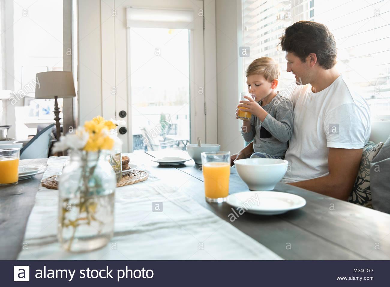 Celebración padre hijo tomar jugo de naranja en el rincón desayunador Imagen De Stock