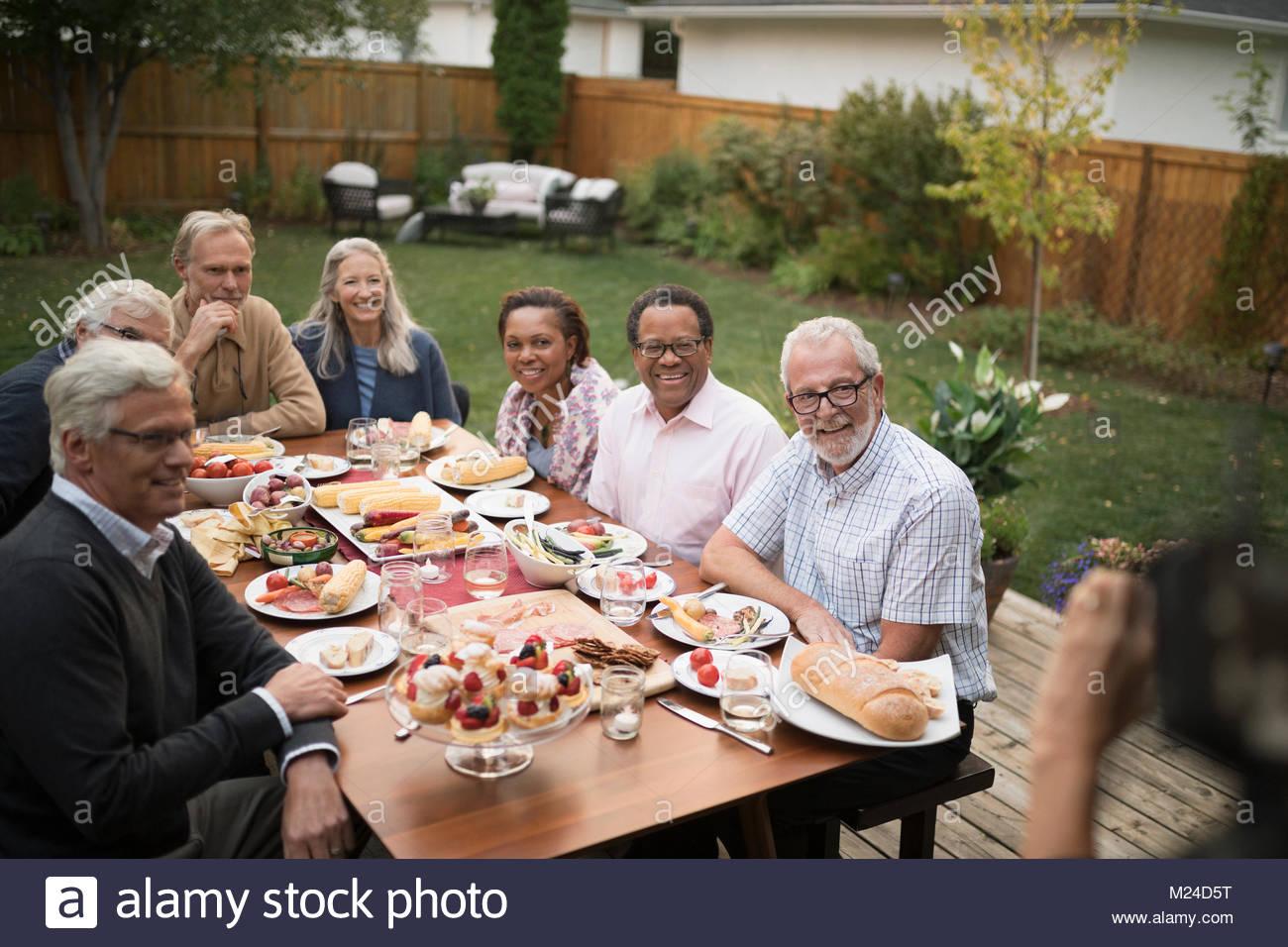 Altos amigos posando para la fotografía, disfrutando garden party almuerzo en mesa de patio Imagen De Stock