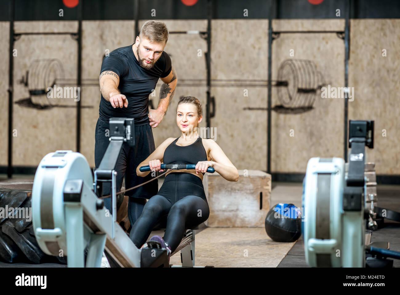 Mujer de capacitación para entrenadores en la máquina de ejercicios Imagen De Stock