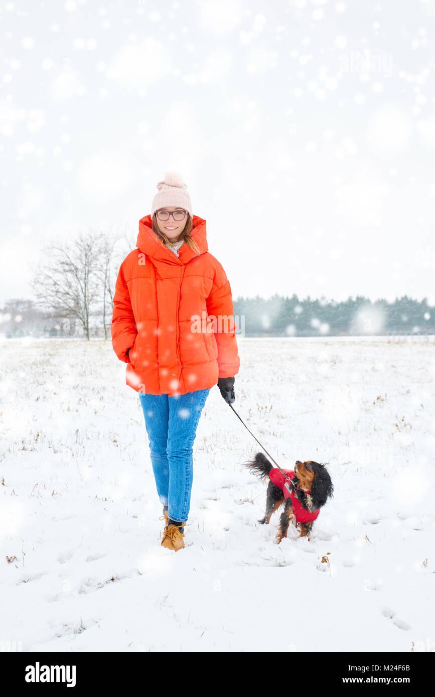 Disparo de longitud completa de una mujer alegre y caminar su perro pequeño al aire libre en invierno. Imagen De Stock