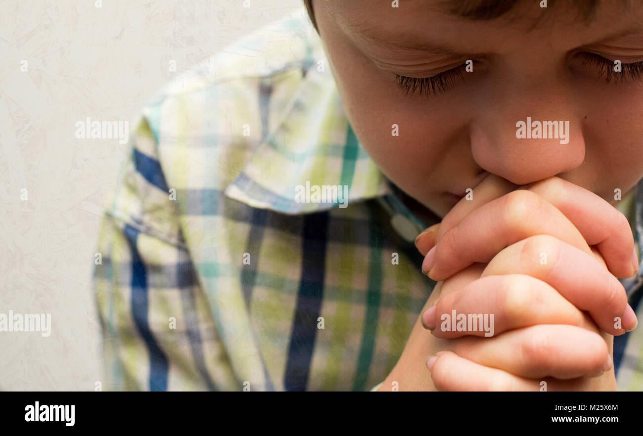 Un muchacho con su cabeza inclinada en oración Imagen De Stock