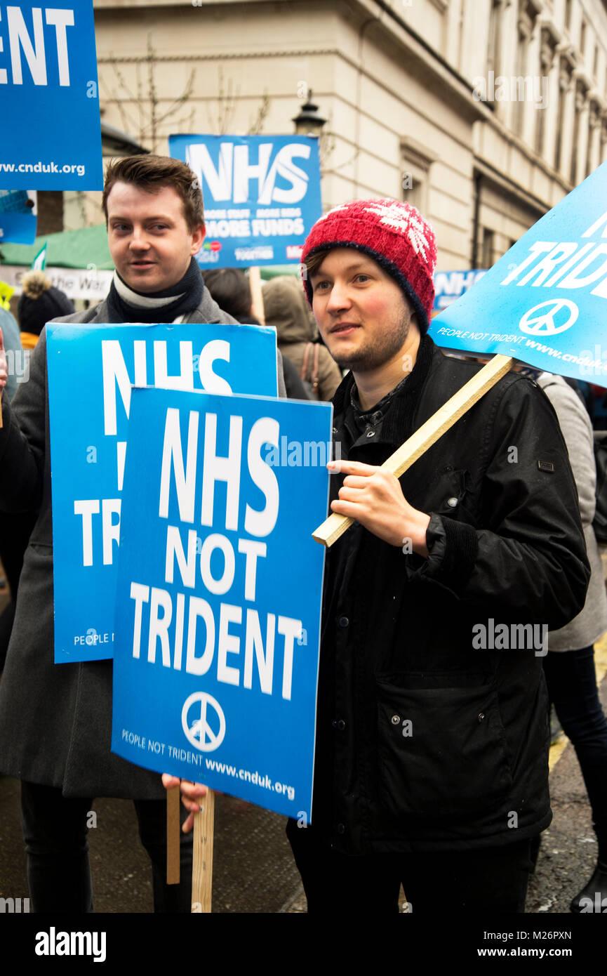 Manifestación convocada por la Asamblea Popular en apoyo del NHS . Dos jóvenes hombres sostienen carteles Imagen De Stock