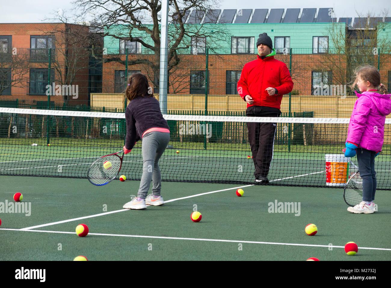 Sesión de entrenamiento de tenis para niños / lección teniendo lugar sobre una pista de tenis de Imagen De Stock