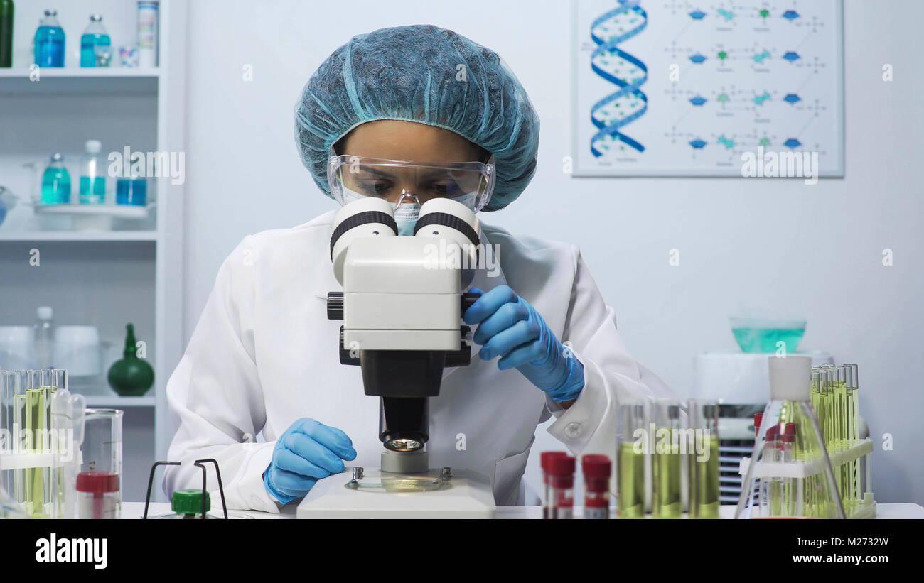 Hembra atento ayudante de laboratorio haciendo la investigación médica, mirando al microscopio Imagen De Stock