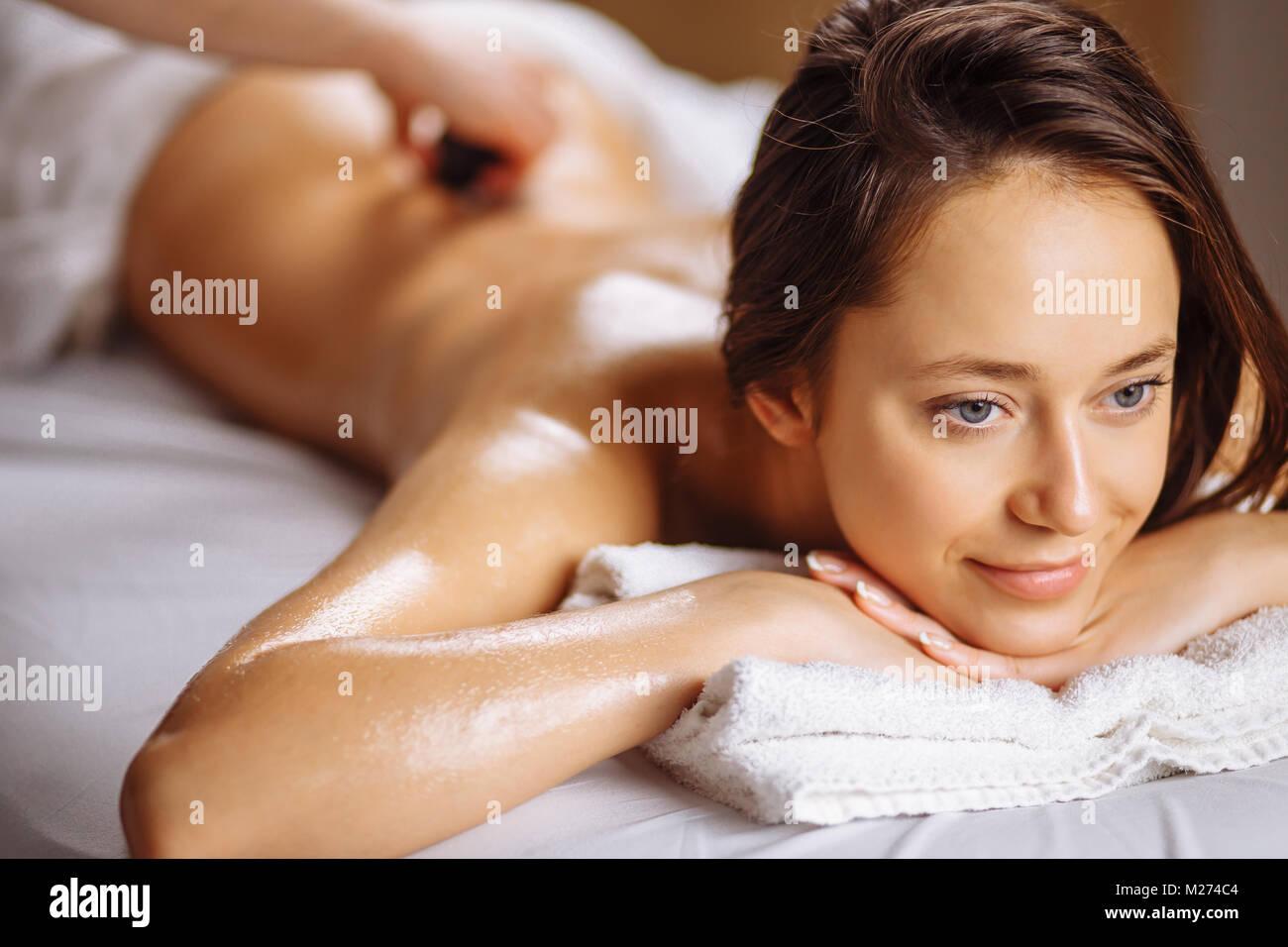 Mujer joven obteniendo el masaje con piedras calientes en el salón spa Imagen De Stock