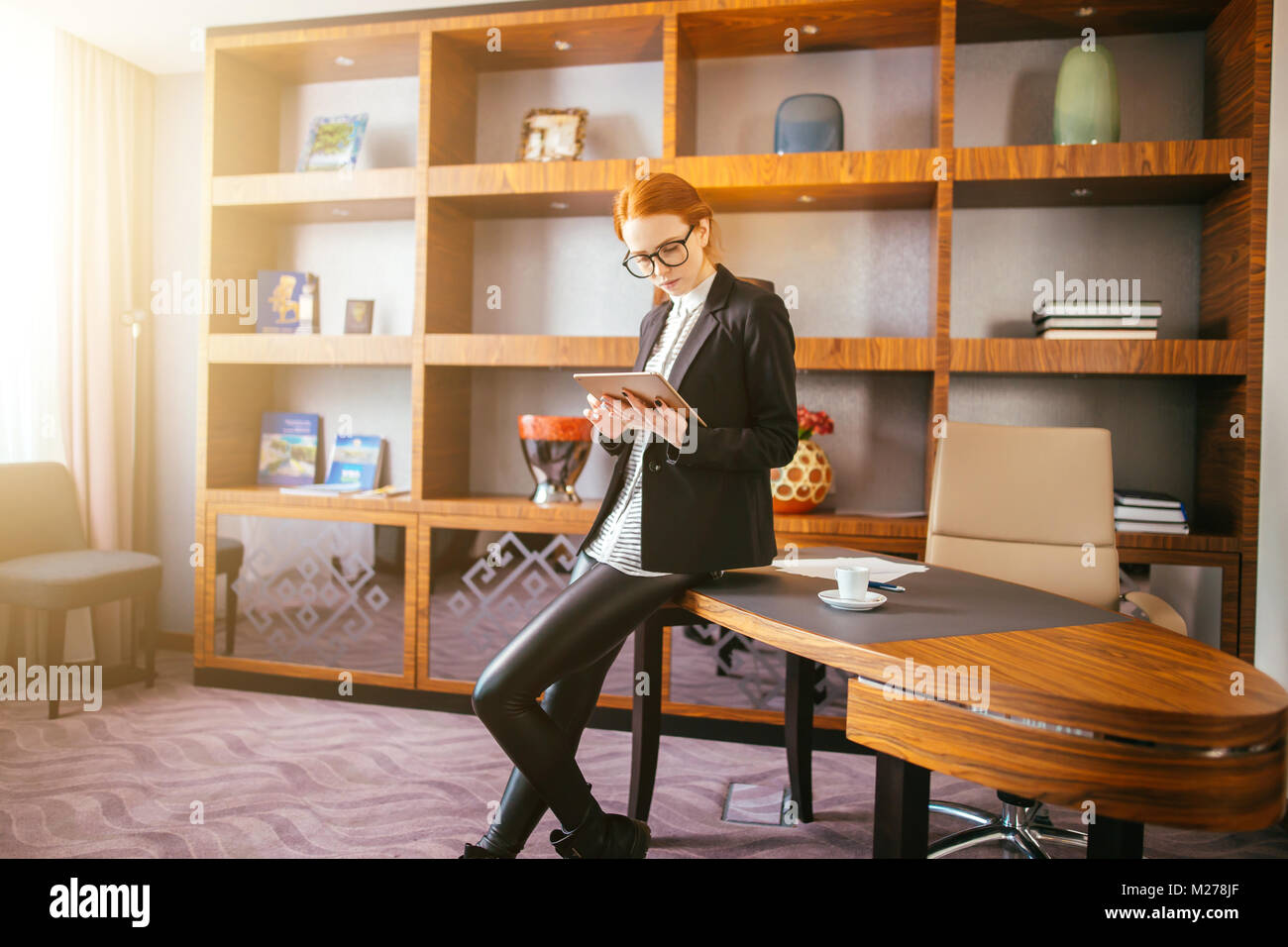 Atractiva empresaria trabajando en una tableta digital en la oficina. Imagen De Stock