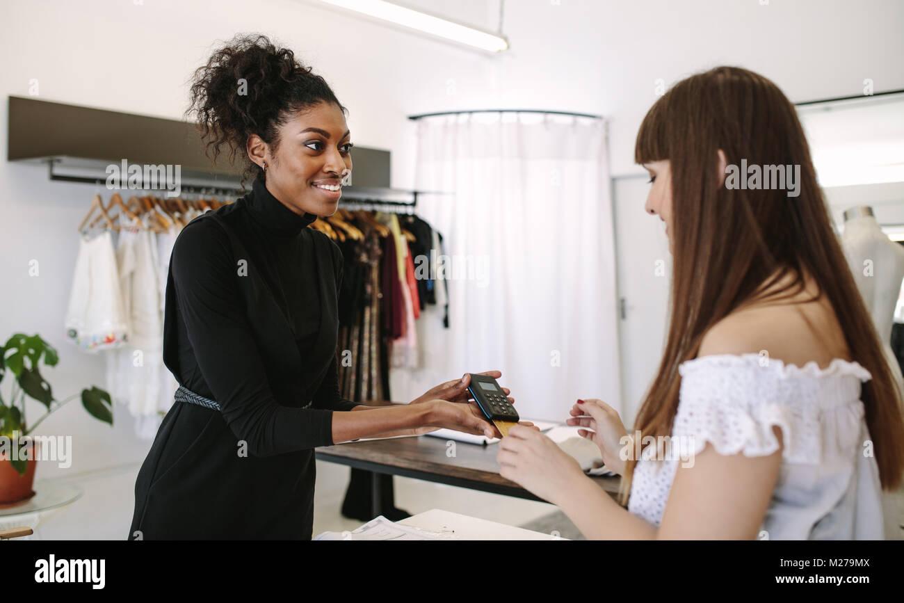 Diseñador de compras del cliente desgaste en una boutique de moda. El cliente, haciendo el pago con tarjeta Imagen De Stock