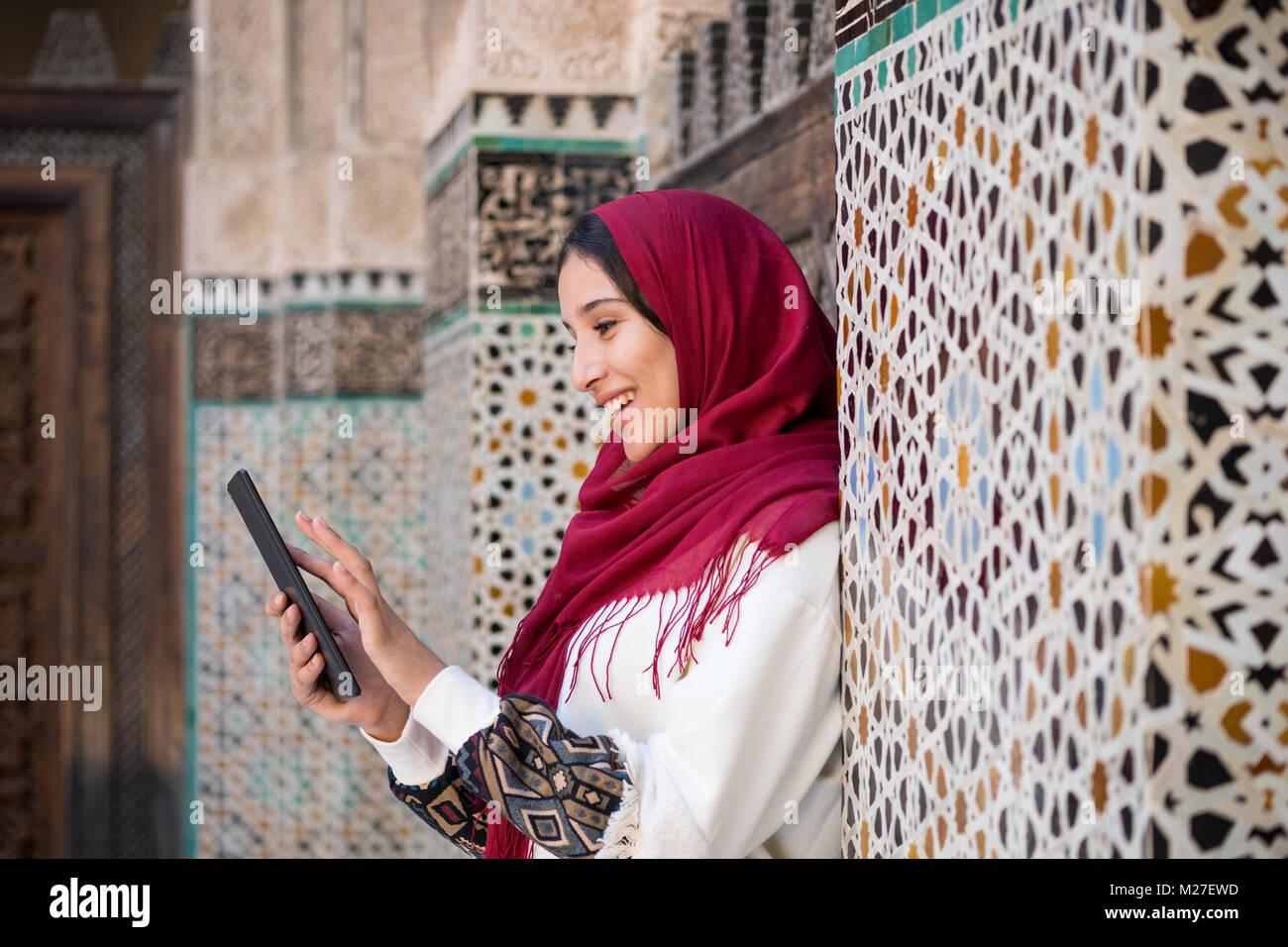 Sonriente mujer árabe en vestimentas tradicionales con pañuelo rojo sobre su cabeza trabaja en Tablet PC Foto de stock
