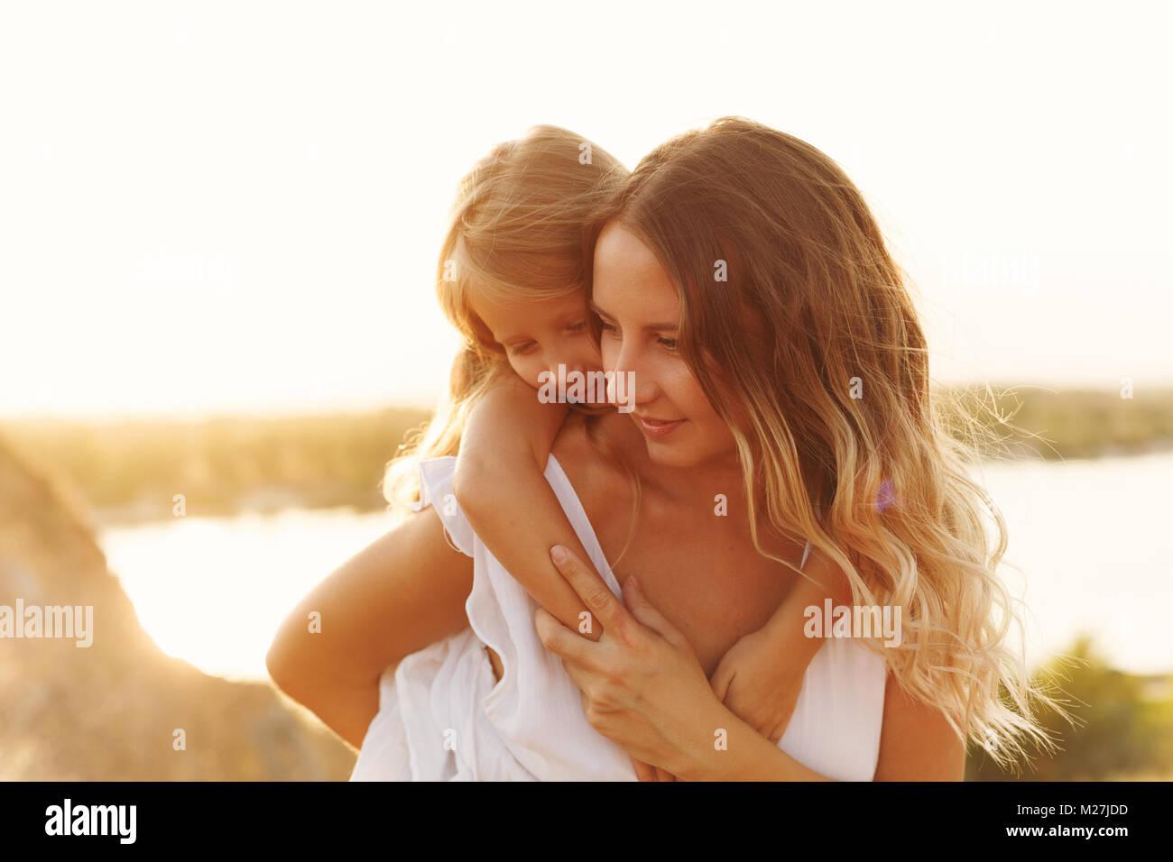 La familia, la madre y la hija en el banco del río. Una niña lleva a su hija sobre sus hombros piggyback. Imagen De Stock