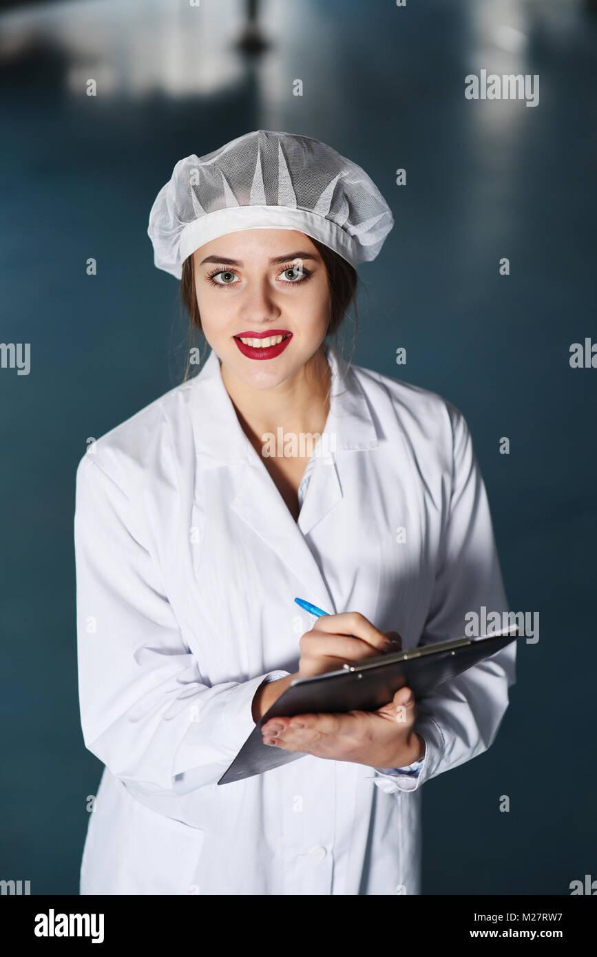 Una chica bastante joven científico o trabajador en blanco uniforme hace que las notas en papel, con el telón de fondo de la moderna fábrica de equipos. Foto de stock