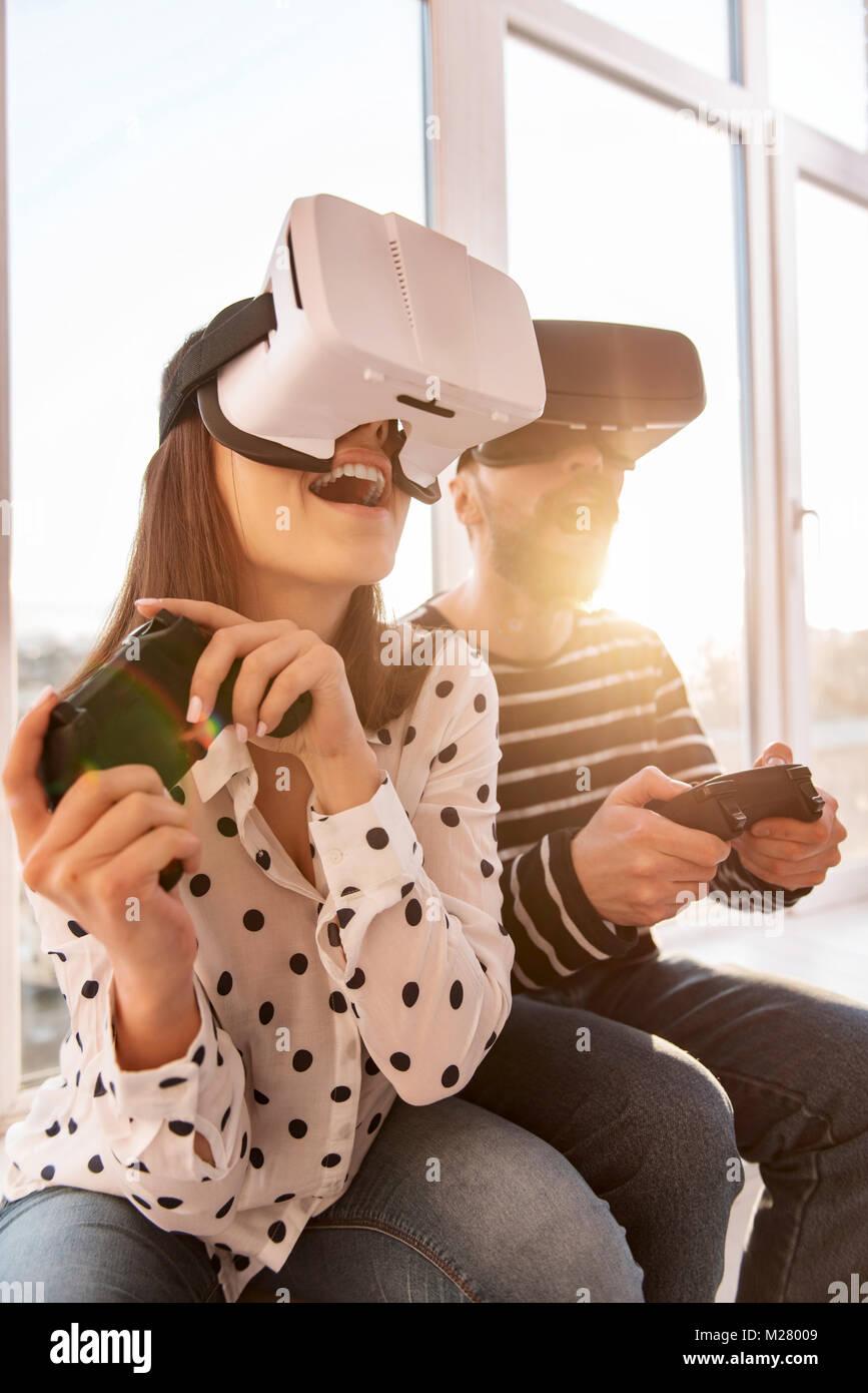 Sobresaltado hermosa mujer iniciar juego VR Foto de stock