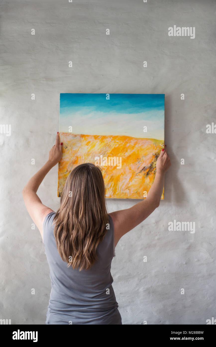 Mujer colgar un cuadro en la pared Foto & Imagen De Stock: 173517565 ...